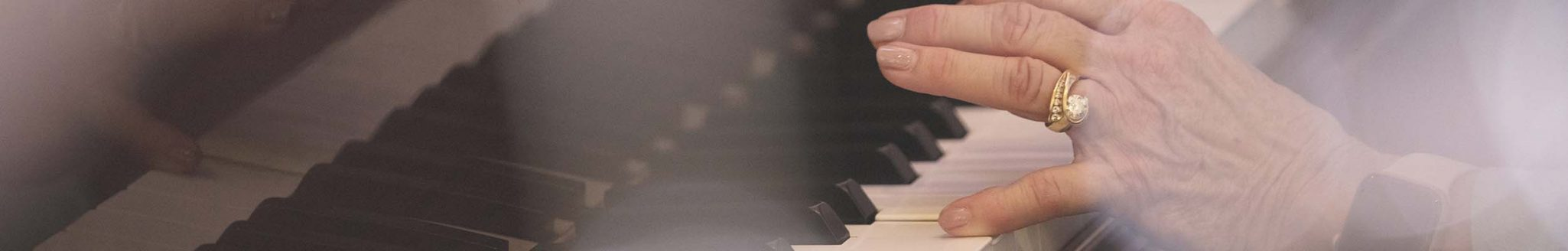 A close up photo of a senior woman playing the piano