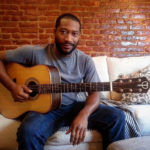 Toney Rocks, relaxed on a white couch with his Teton Guitar