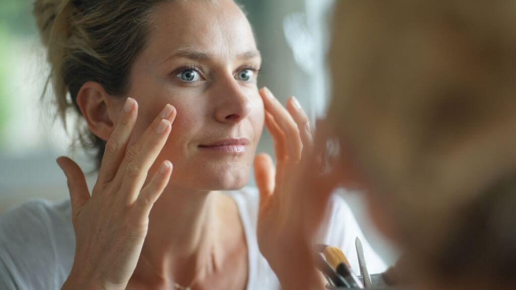 A woman applying toner to her face.