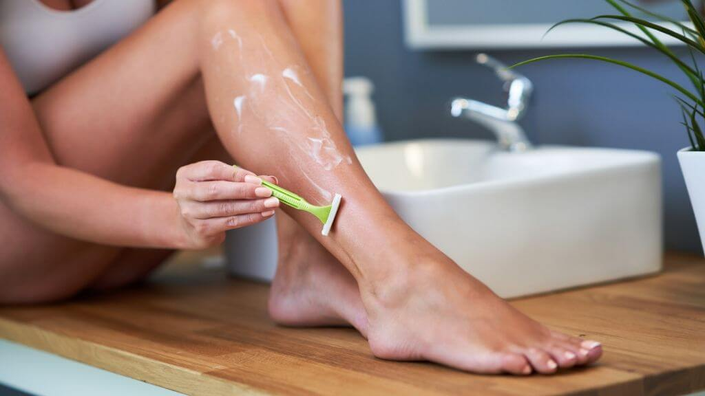 A woman shaving her leg.