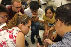 A group of IAESTE students and interns looking at a design of Katagami from the expert's phone.