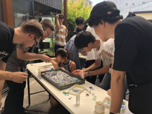 Making chopstick rests from pieces of glass during the Kawagoe summer program.