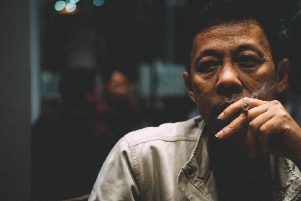 Asian man smoking outside