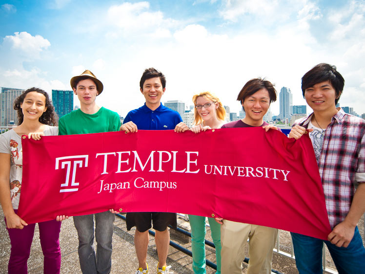 Scholarship recipient of Temple university holding a banner