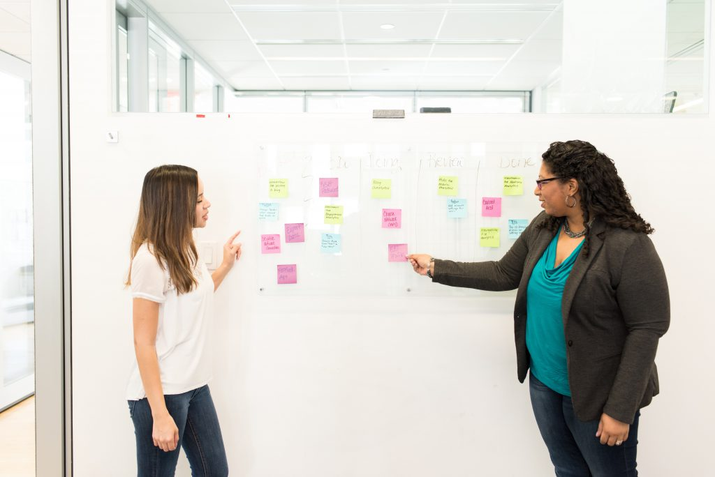 two girls brainstorming ideas on wall