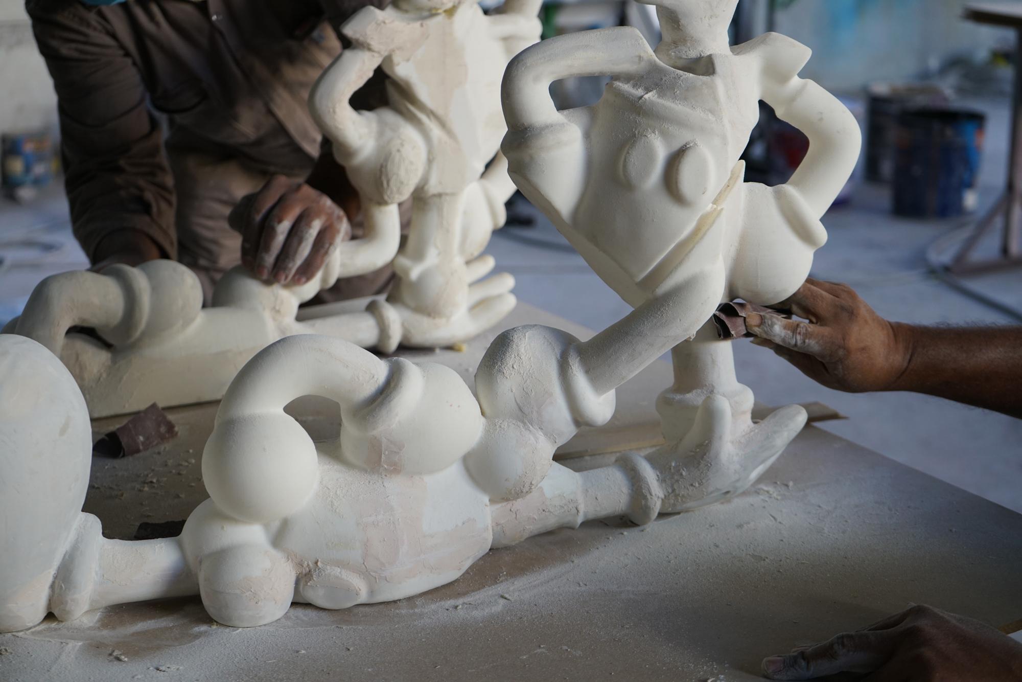 hands sanding white plaster sculpture