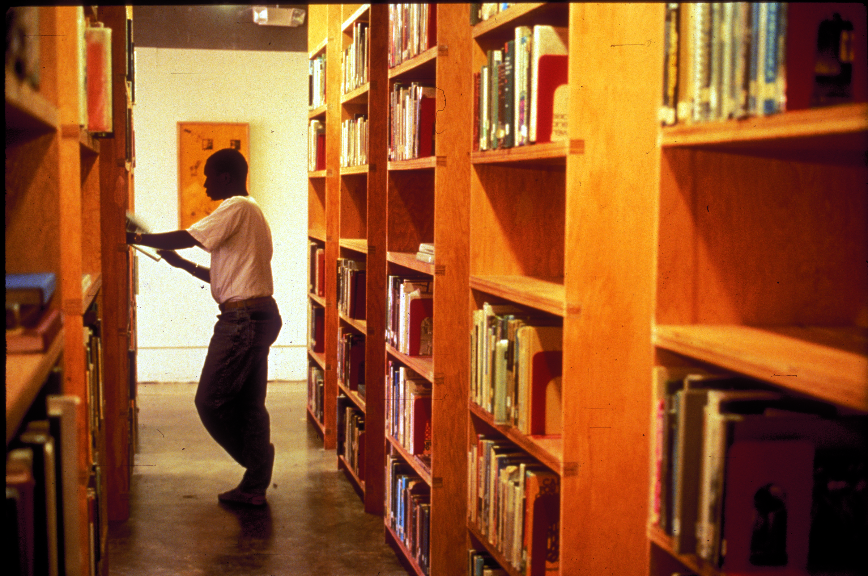standing man reads book at bookshelf