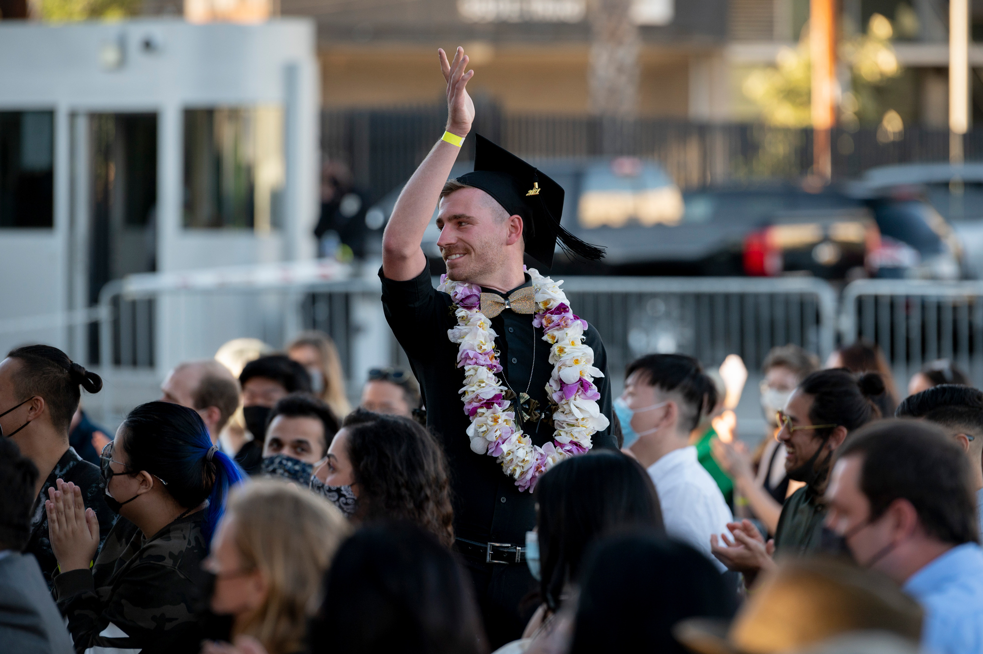student celebrating graduation crowd