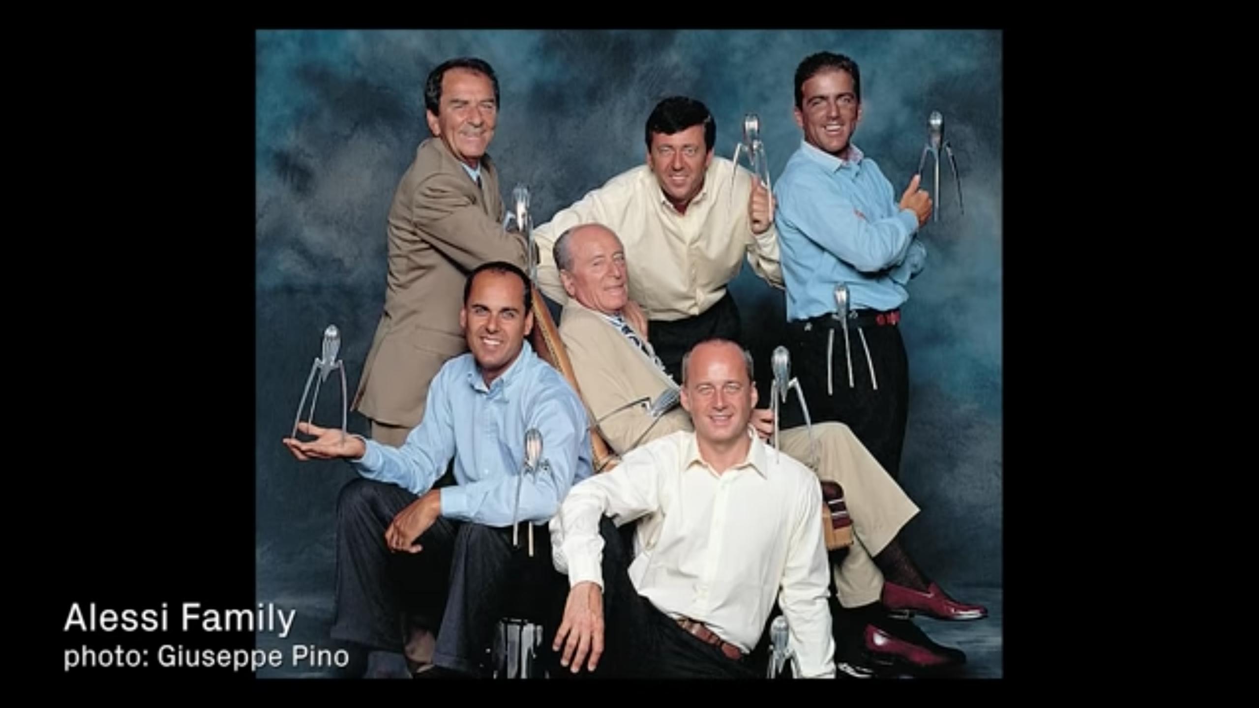 group of men smiling holding sculptures