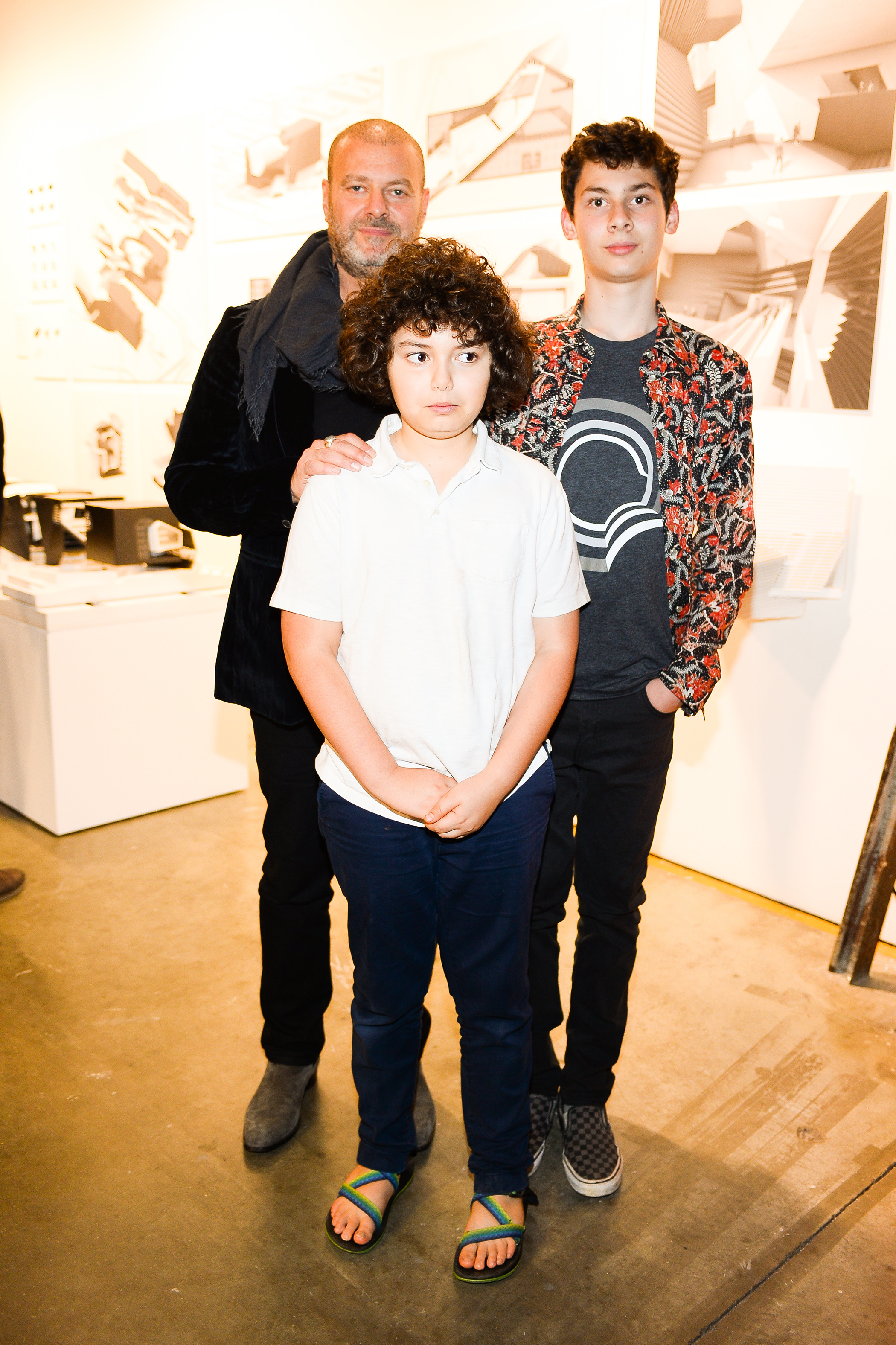A man and two boys stand and pose for a photo together.