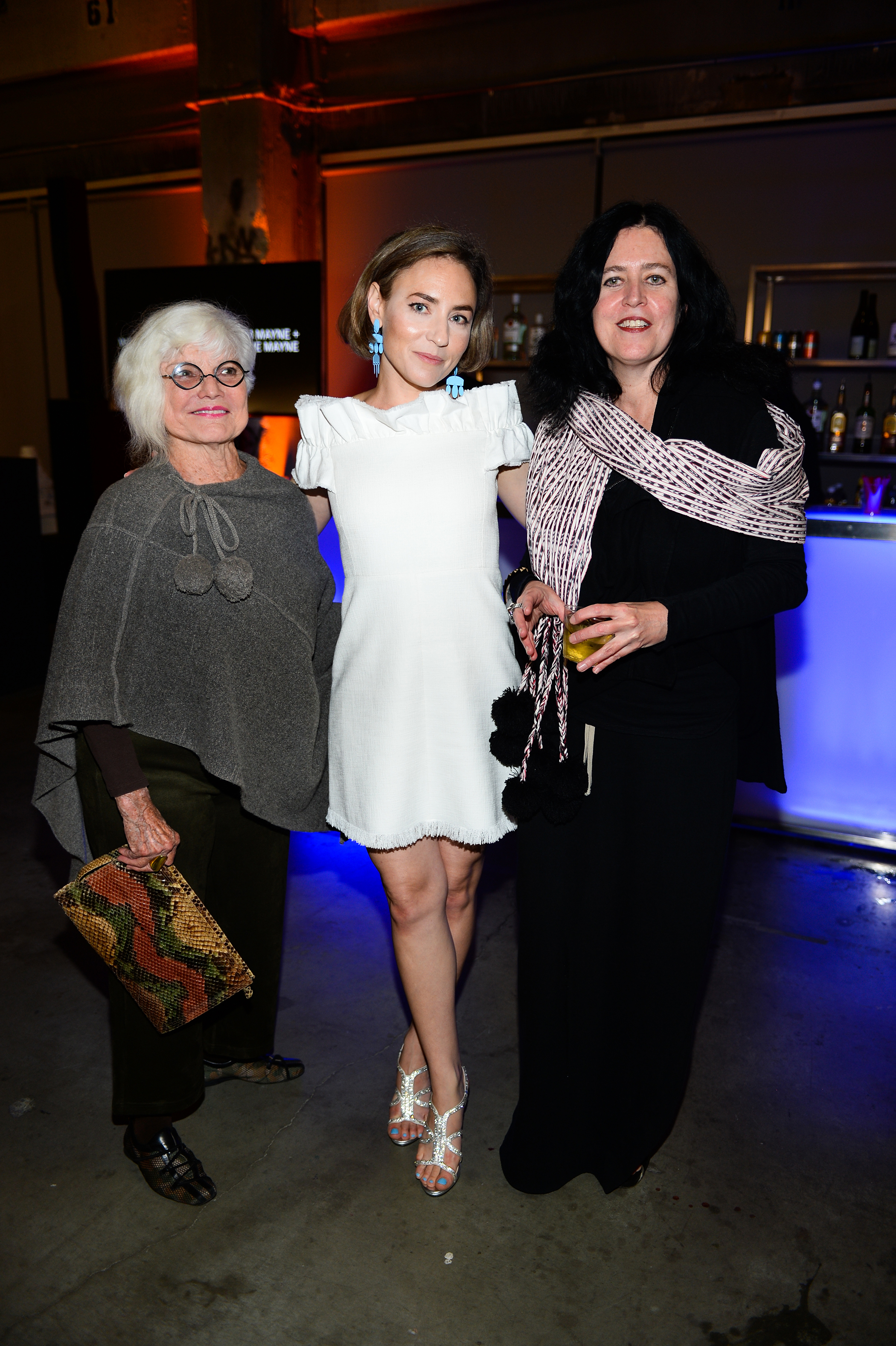 Three women stand and pose for a photo together.