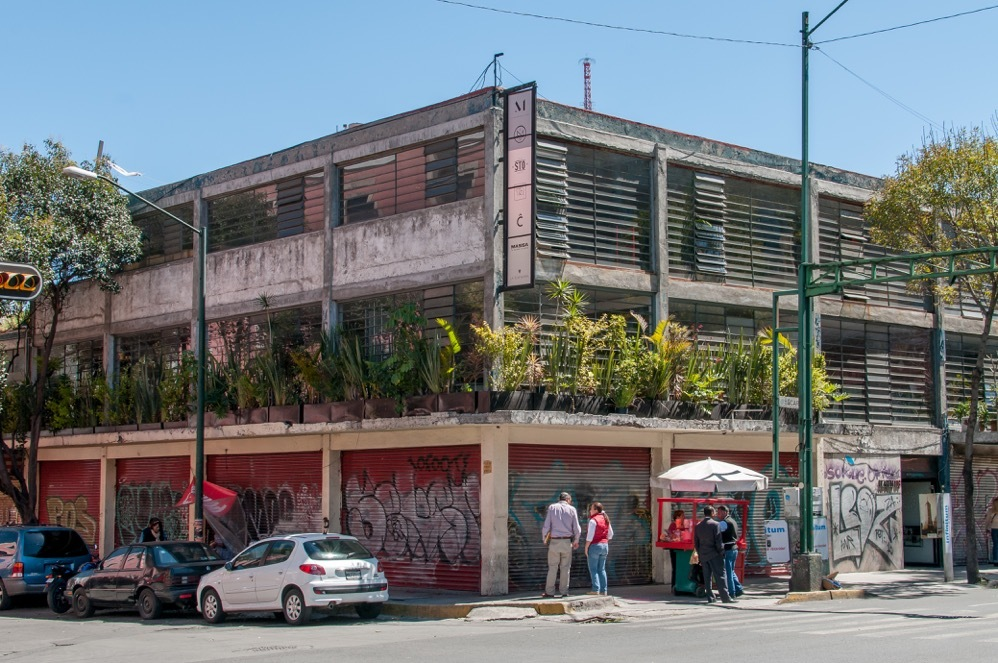 an old concrete building with potted palnts on second floor and graffiti on the walls