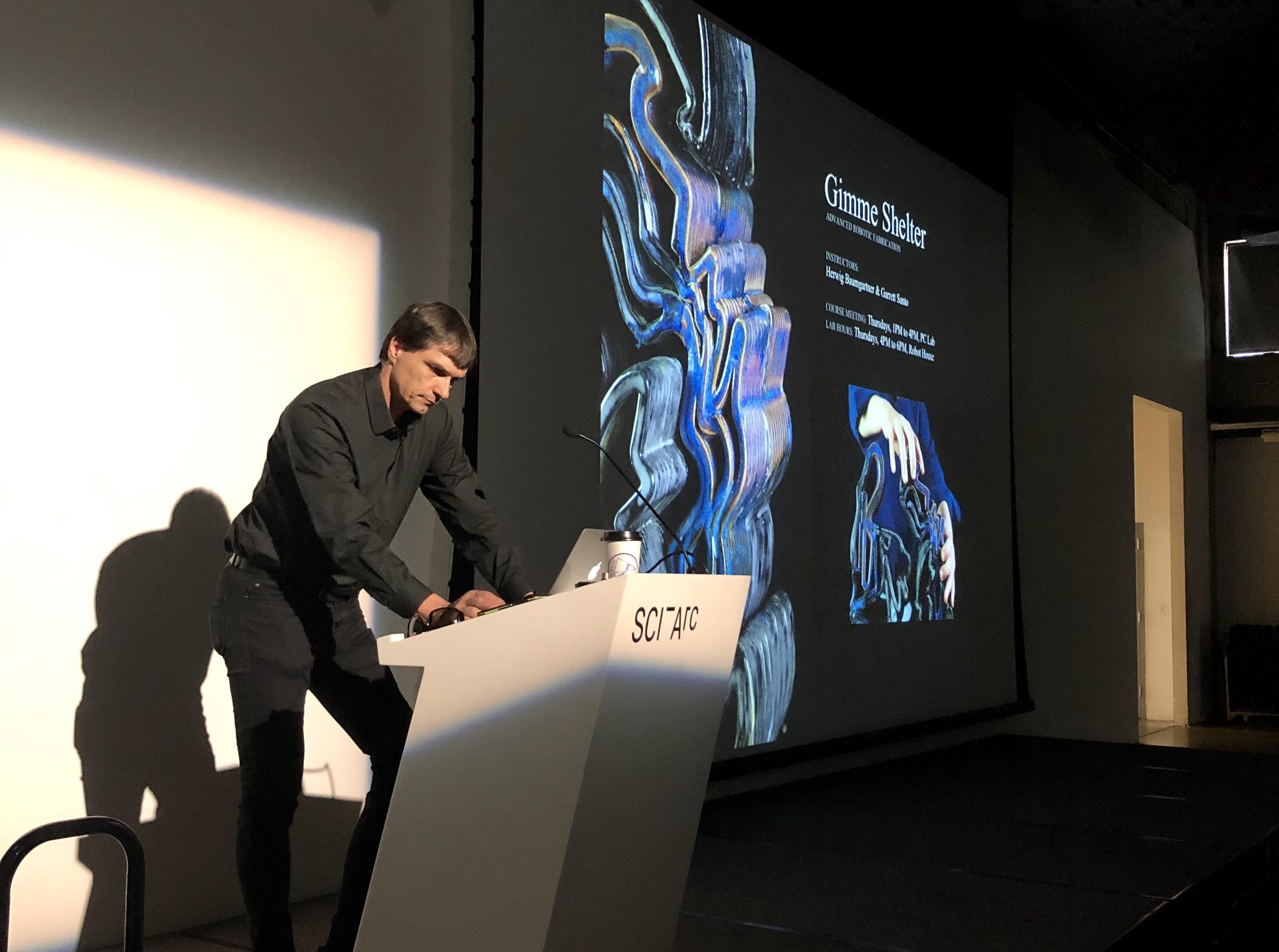Herwig Baumgartner standing at podium presentation