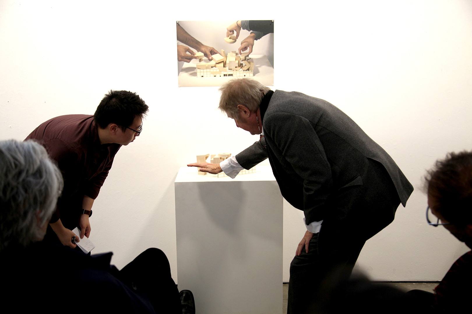 SCI-Arc faculty discussing with a student on an model during presentation