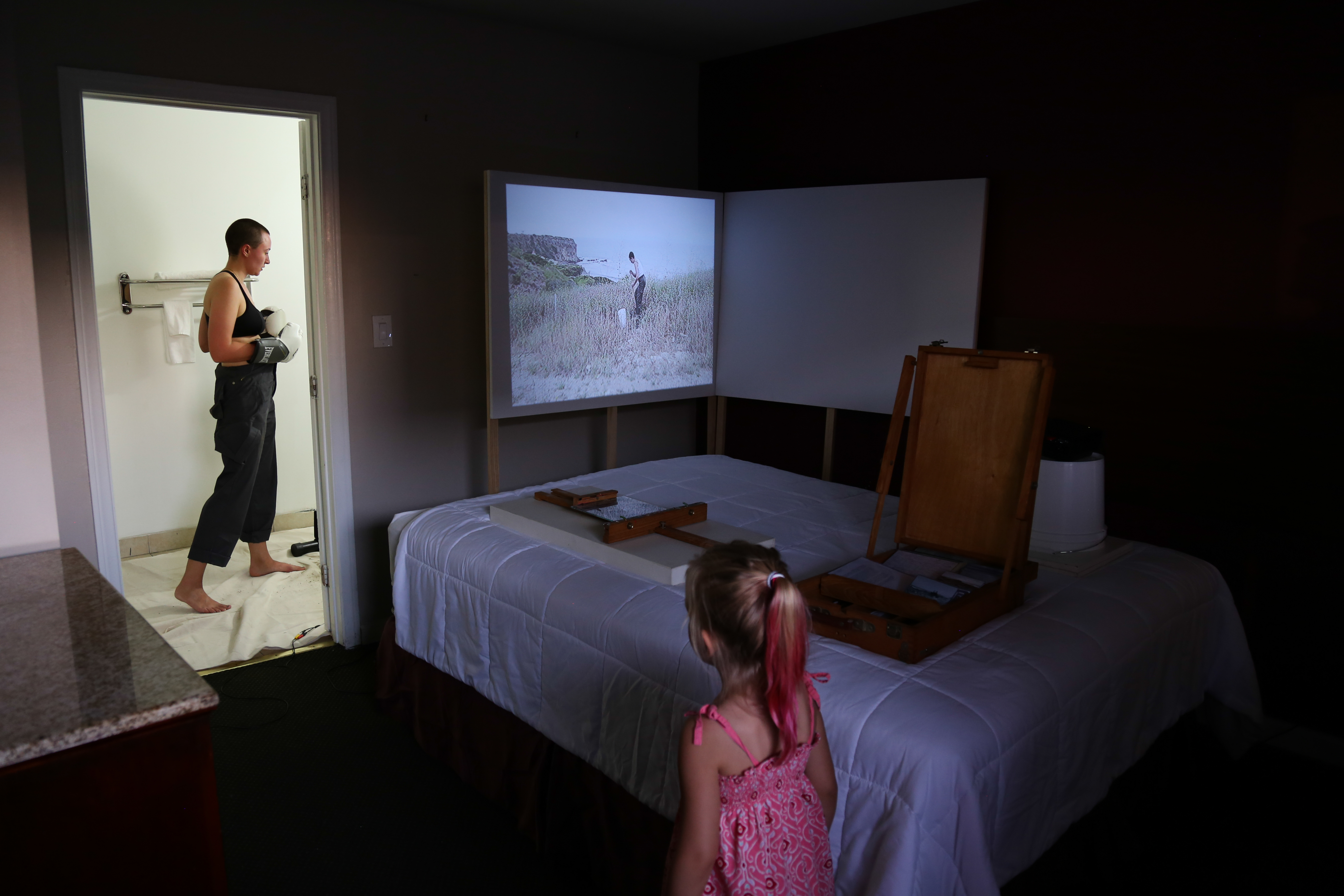 a dark room with a bed in corner with a little girl and a lady in boxing gloves