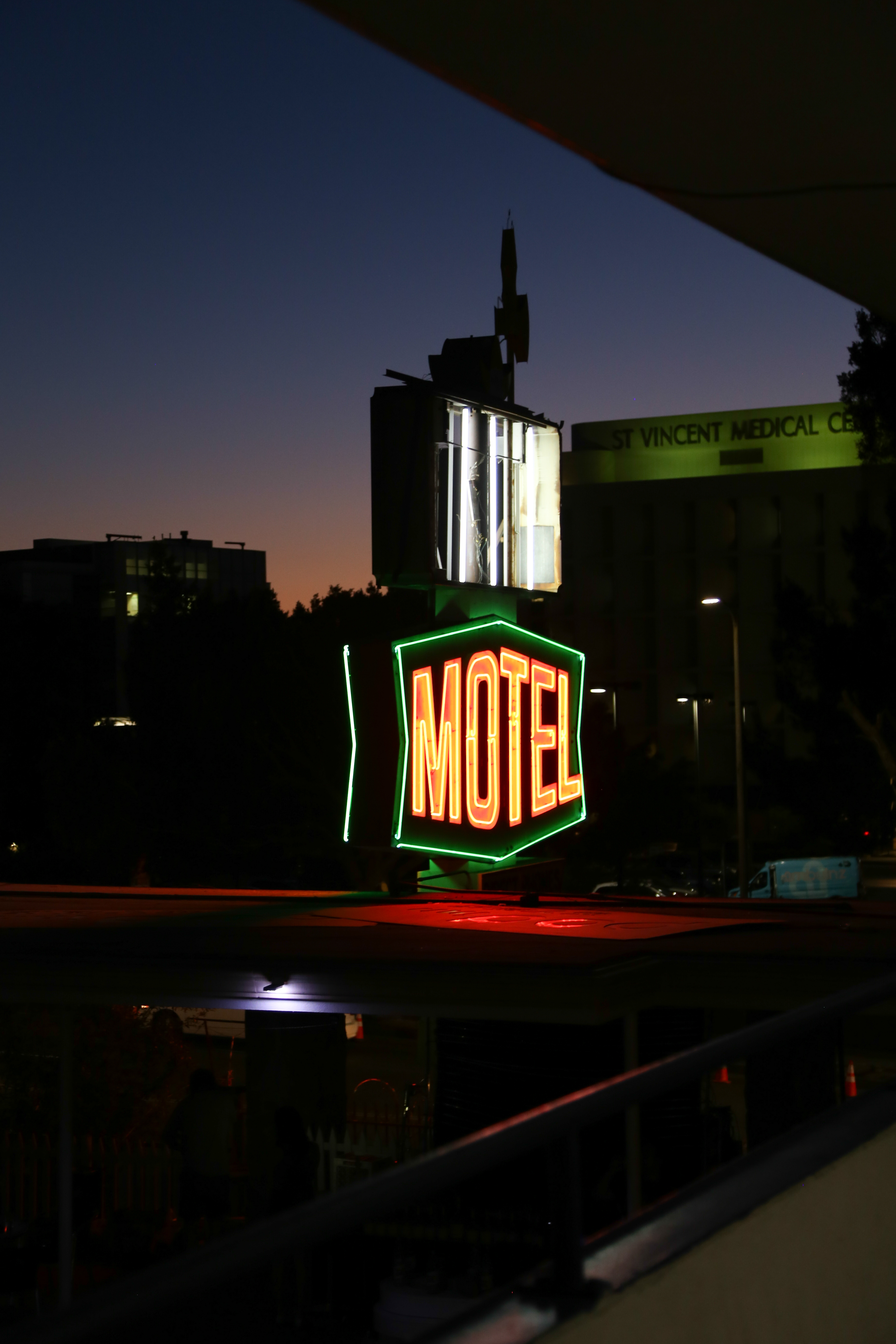 a neon light symbol with green borders and yellow text reading Motel