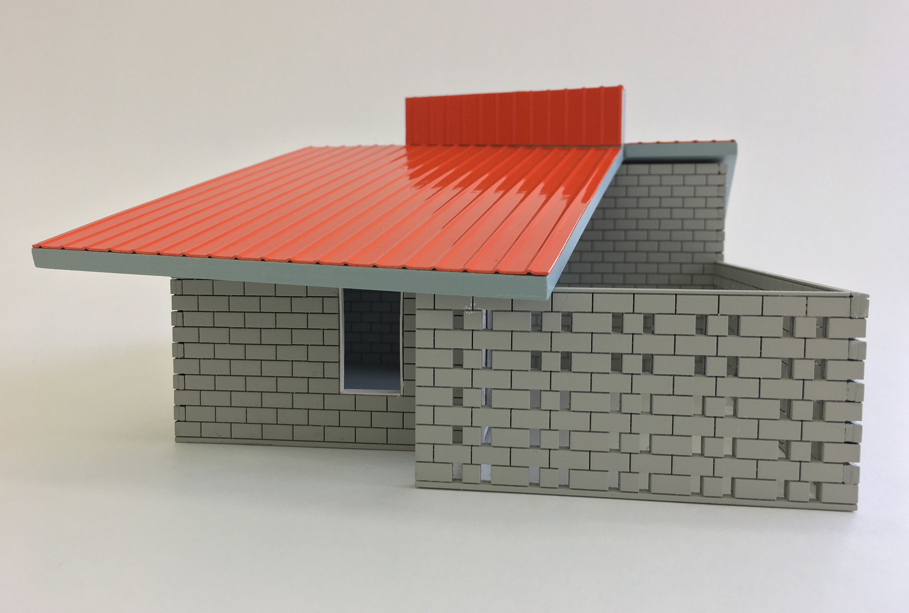 Architectural model of house with grey bricks and orange roof
