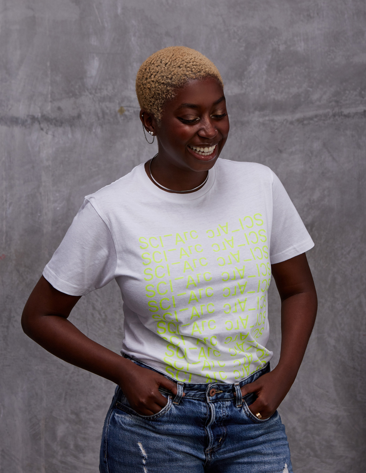 female in neon on white sciarc logo tee shirt