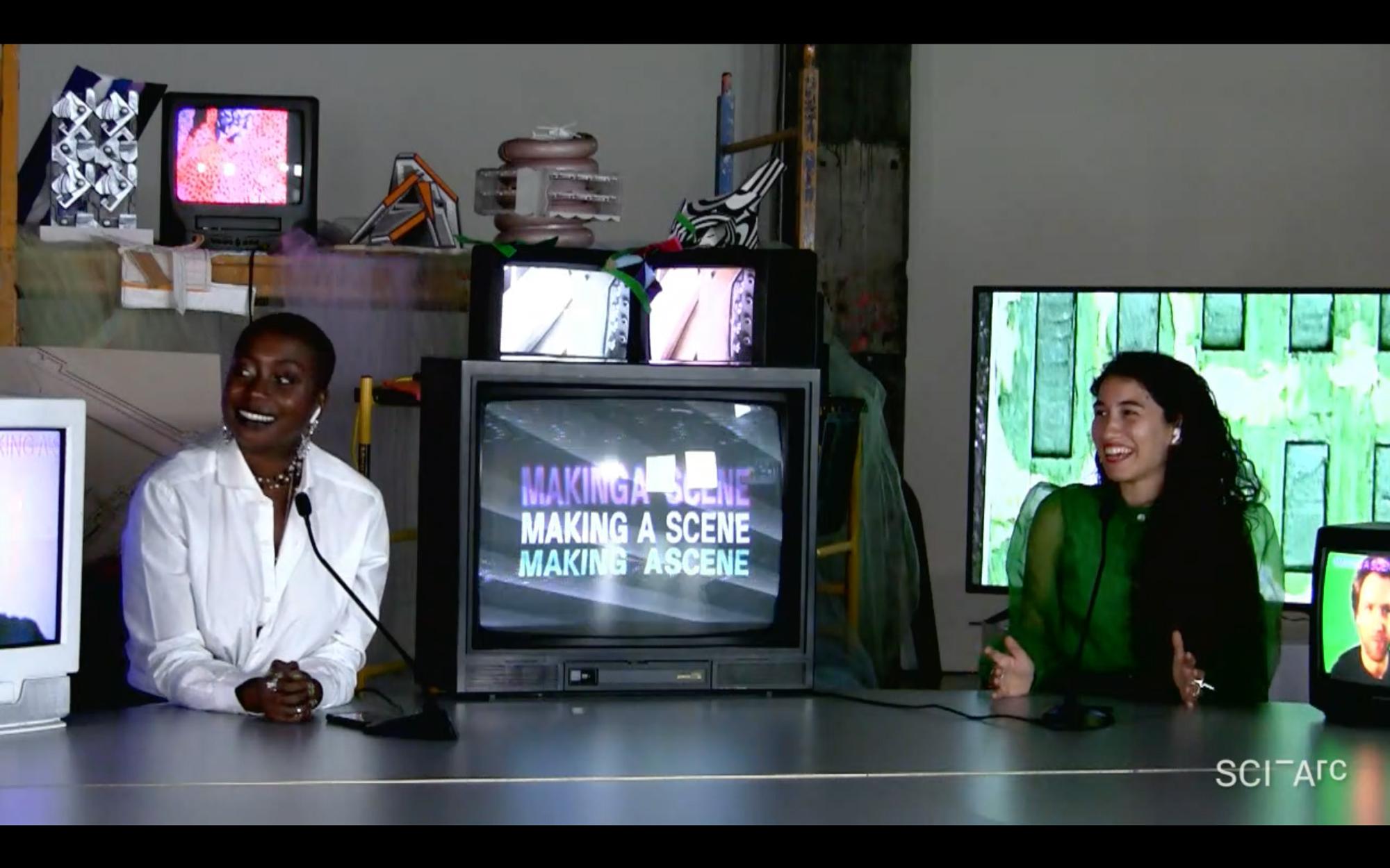 women smiling sitting between tv screens