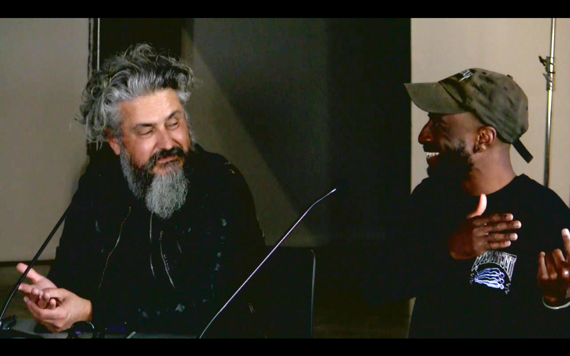 two men discussing smiling mic
