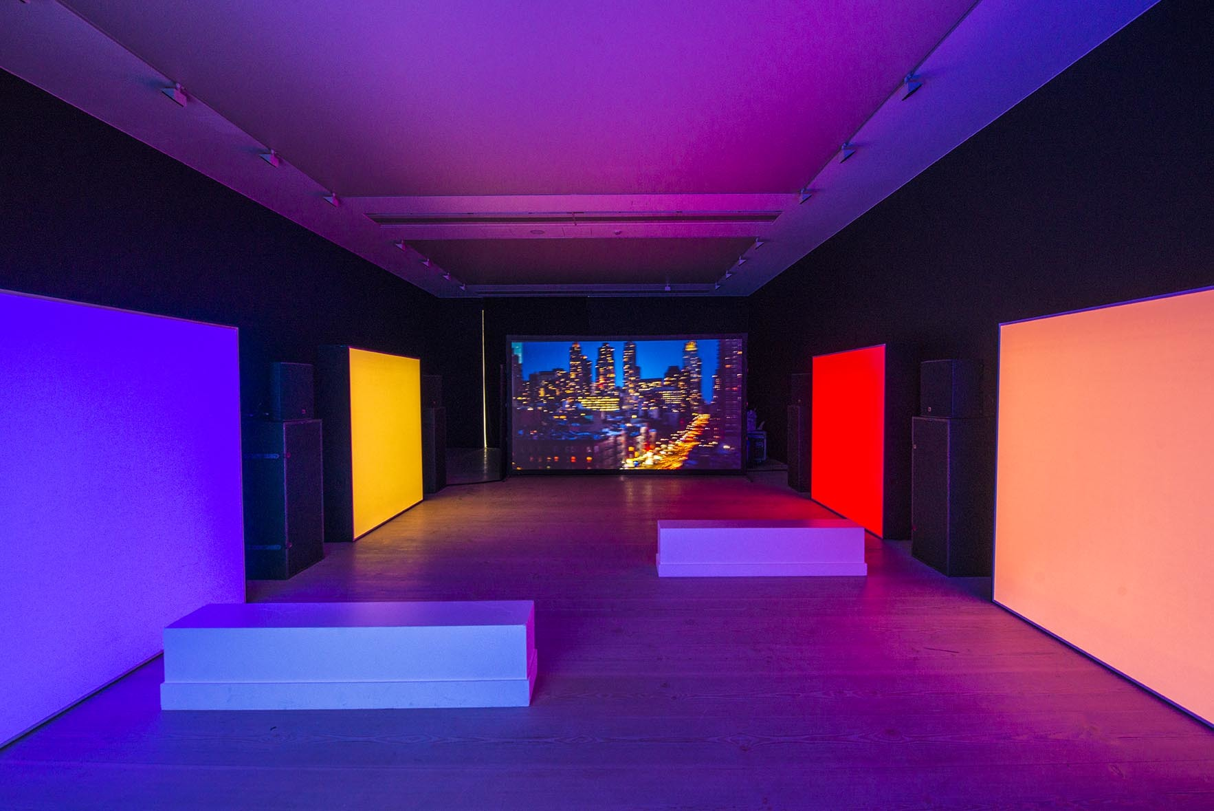 lit up prime colored boxes within dimly lit gallery