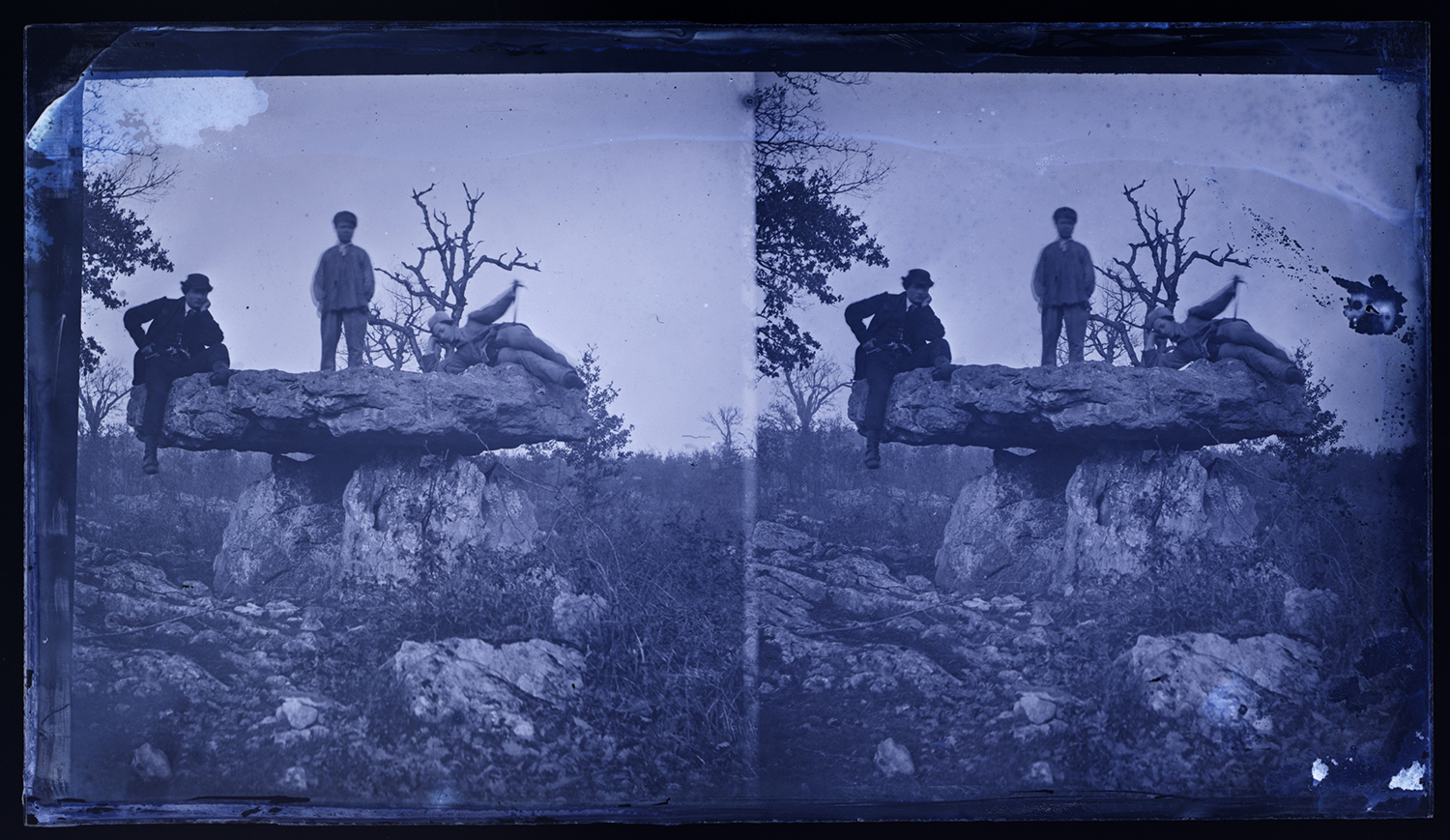 archival photo of two men standing on stone structure