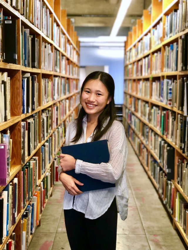 nancy ai smiling amoungst books in library