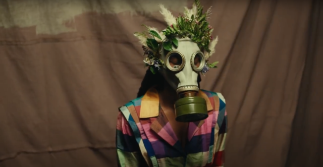 person wearing gas mask decorated in feathers