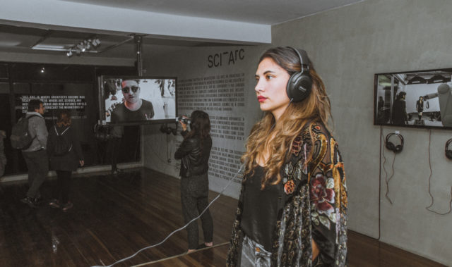 female architecture enthusiast headphones within exhibition