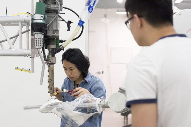 two students and robotic arm build architectural model