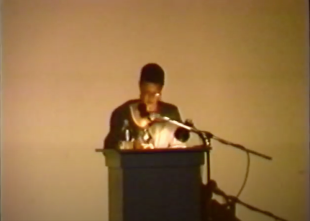 Michaele Pride, a Black female architect, lecturing at a podium in front of a white wall