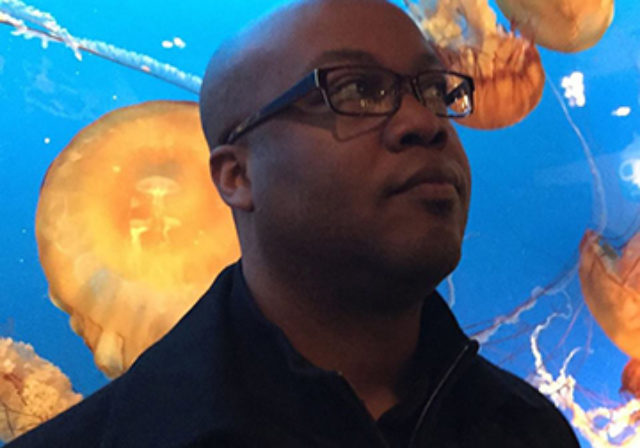 man with glasses in front of jellyfish tank