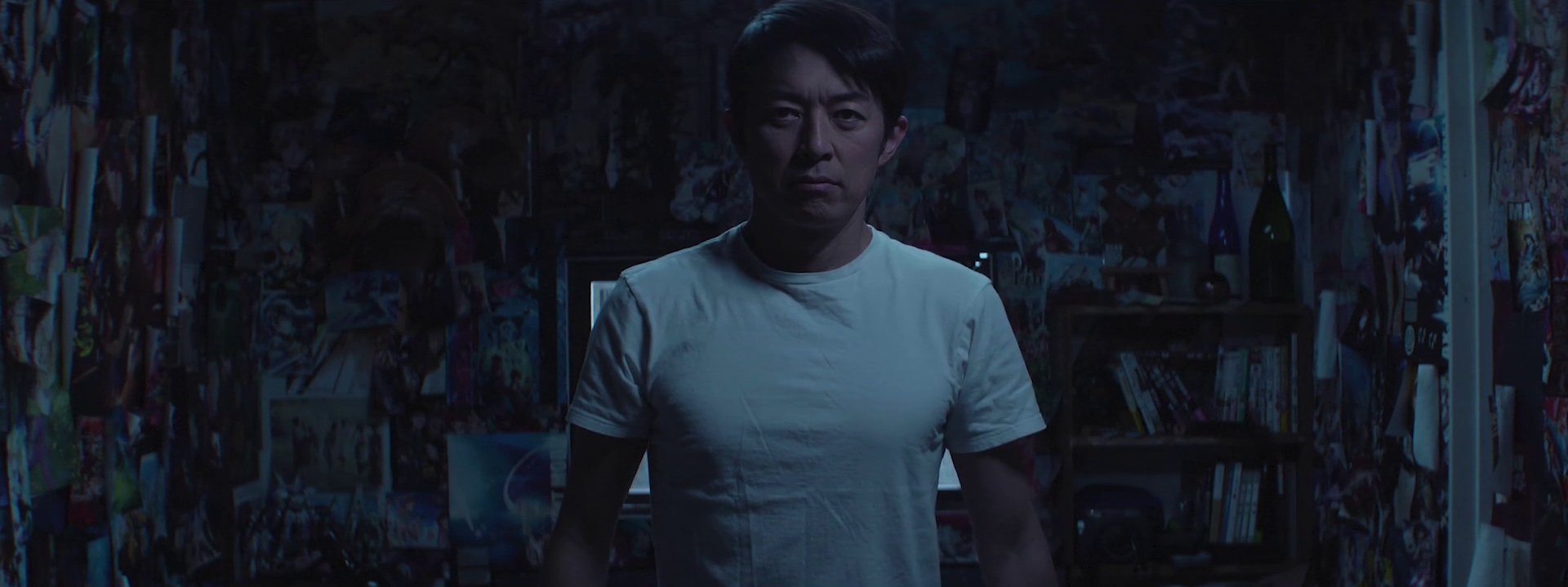 portrait of a Japanese actor in a room where walls are covered with posters