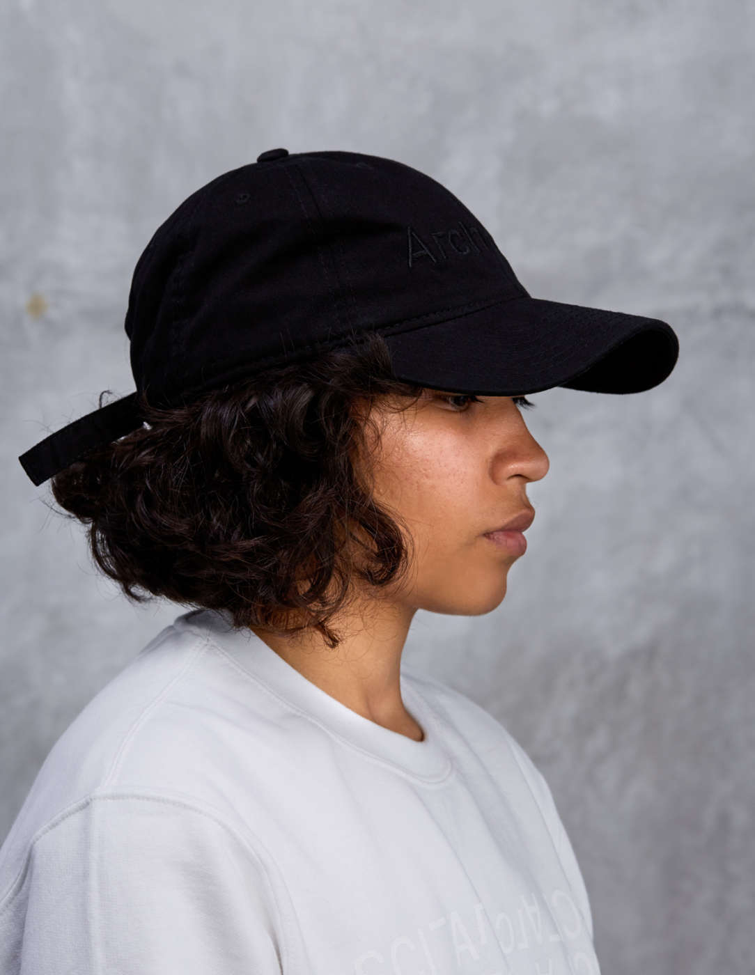 black on black architect logo hat on person