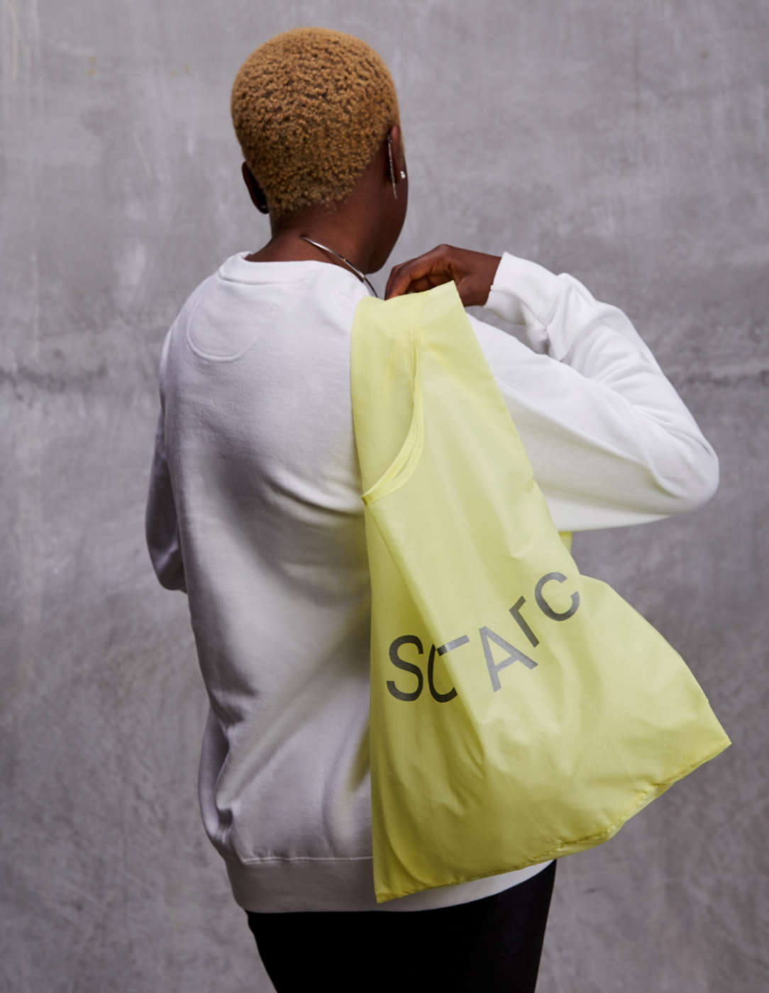 yellow sciarc bag on shoulder of person