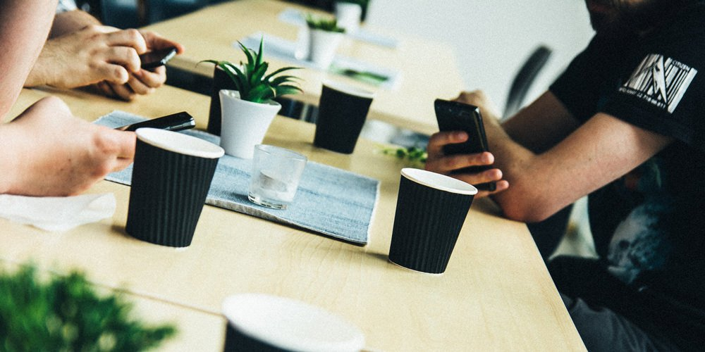 Personer runt ett bord med kaffekoppar och mobiler