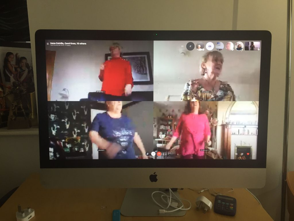 Photo of Zoom session with four screens: with women dancing in their homes