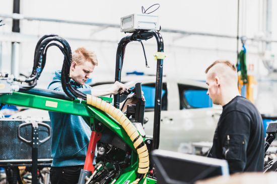 Kaksi opiskelijaa työskentelevät autolabrassa.
