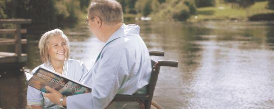 Sairaanhoitaja ja potilas joen äärellä.