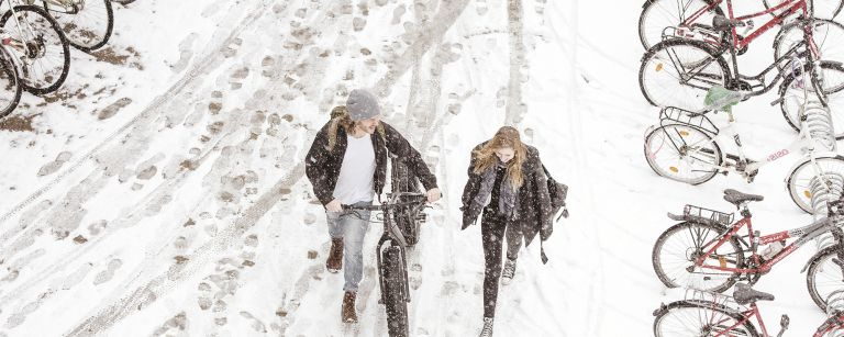 Two students walking with a bike on winter time.