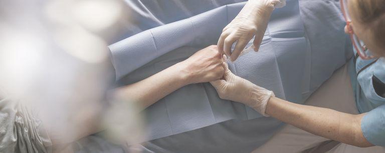 Sairaanhoitaja laittamassa tippaa potilaalle.