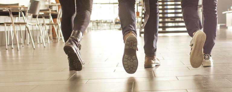 Kävelevien ihmisten jalkoja kuvattuna takaapäin.