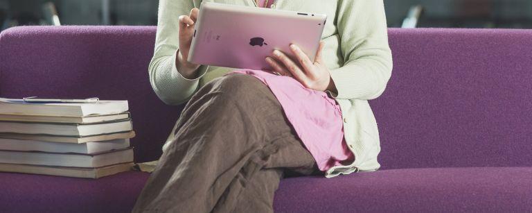 Nainen selaa tablettitietokonetta sohvalla istuen.