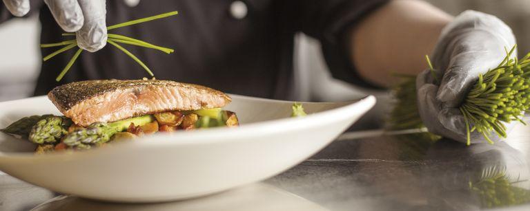 Lohesta on loihdittu maukas à la carte -annos. Ruohosipulia lisätään koristeeksi päälle.