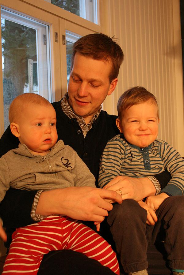 Miehen sylissä kaksi pientä lasta.