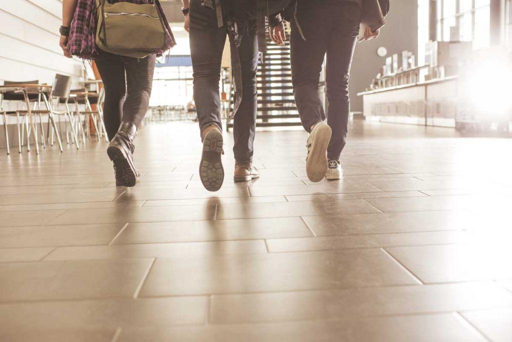 Kolme opiskelijaa kävelee aulassa.