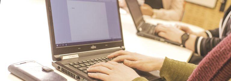 Ihmisiä työskentelee tietokoneilla.