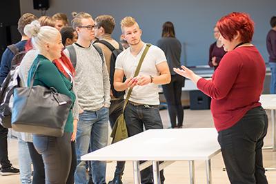 Opiskelijoita kuulemassa yrityksen esittelijää
