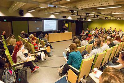 Opiskelijoita vihreässä auditoriossa kuuntelemassa esitystä