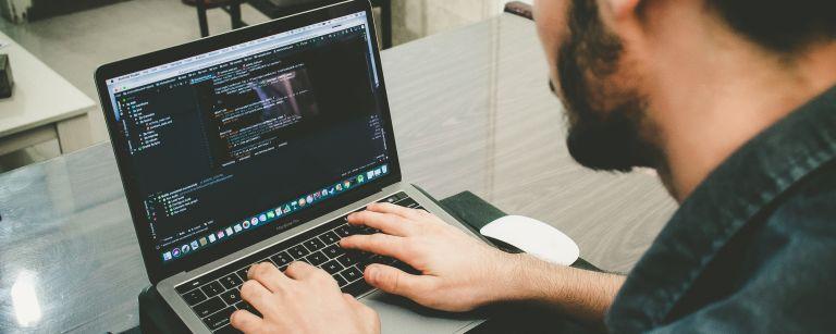 Henkilö koodaa ohjelmistoa tietokoneella.